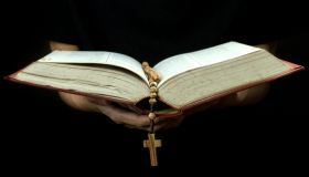 Cropped Hand Of Person Holding Rosary While Reading Bible Against Black Background