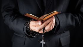 Midsection Of Priest Holding Prayer Beads And Bible While Standing Against Black Background