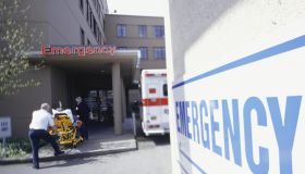 Orderly pushing patient on stretcher into emergency entrance